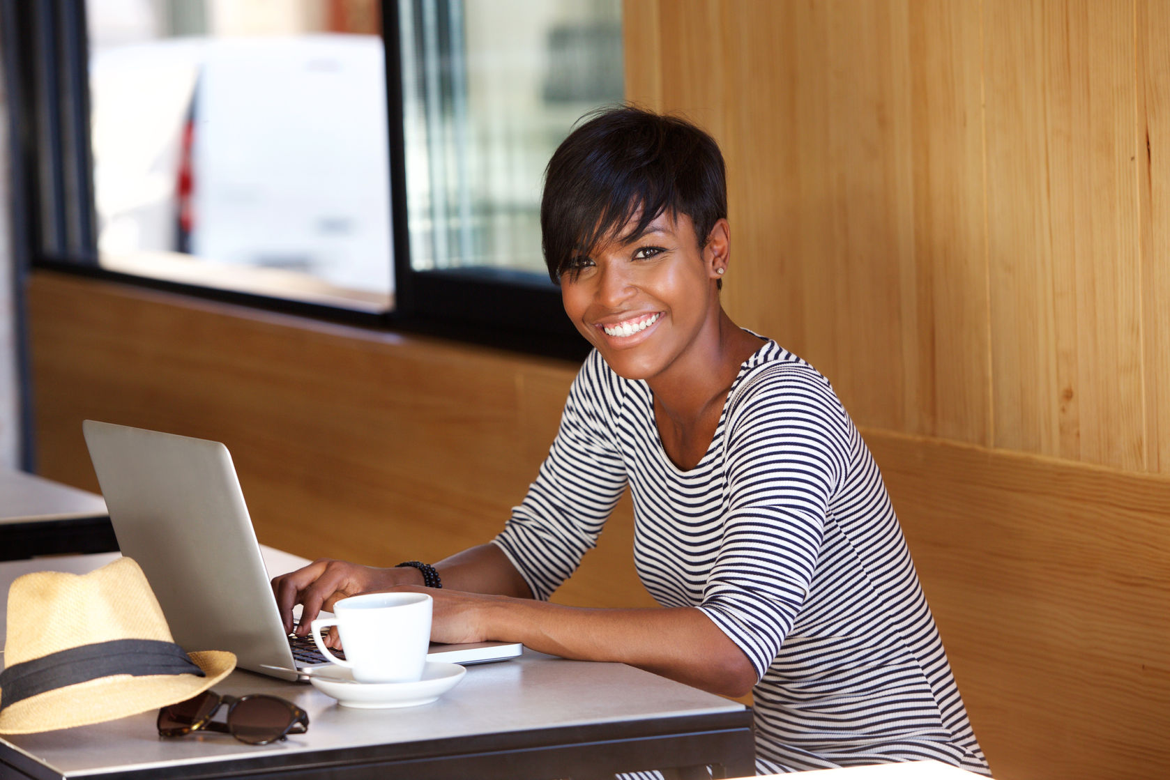 Portrait of a smiling young black woman using laptop